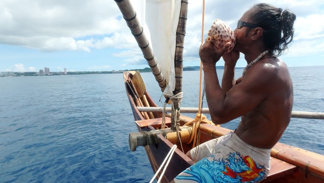 Chamorro canoe builder and seafarer Ron Acfalle blows a kulo' while sailing on one of the hand-built canoes of his group, Ulitao, on July 30, 2015.