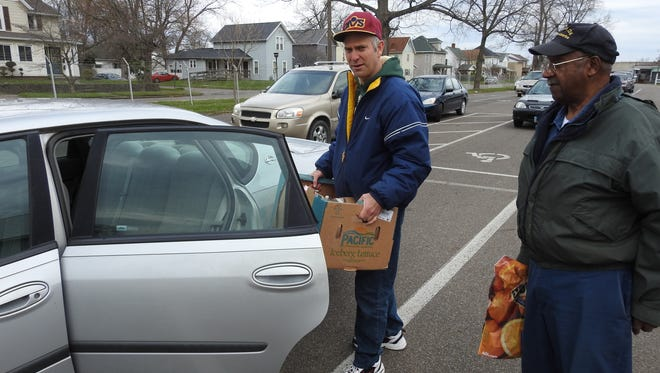 Teacher Shawn Cheney of the Coshocton Opportunity School  loads fresh produce and staples into the car for Zelek Taylor of Coshocton at this week's free Produce Market at the Coshocton County Fairgrounds.