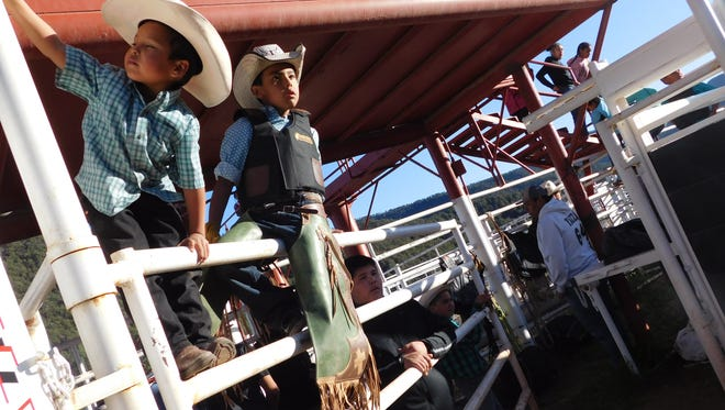 A young cowboy intently watches the action in the Sampson Miller Arena while another is focused on his own entertainment.