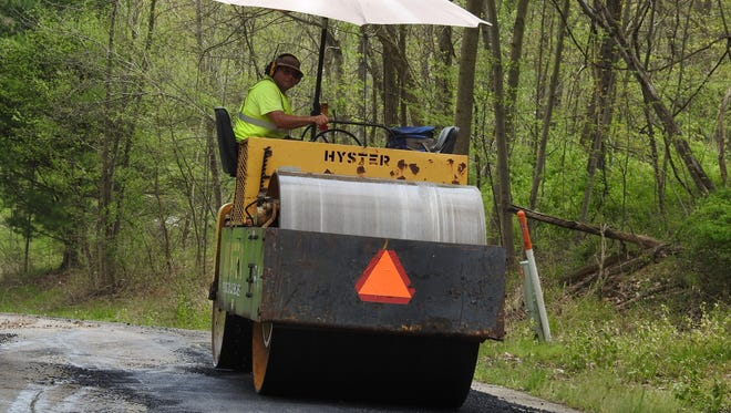 Highway Maintenance Worker Chris Guthrie rolls asphalt along County Road 227 in Crawford Township after crews had leveled the existing roadway.