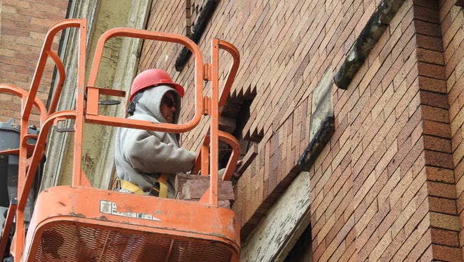 Dan Weaver, of Marion, Ohio, repairs masonry on the front of Coshocton's Shiloh Missionary Baptist Church. More repairs are needed, according to the Rev. Cliff Biggers.
