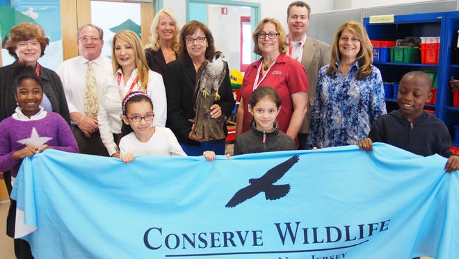 Front row, left to right, Linden School No. 4 third-grade students Daneysha Izajar Montano, Tilelli Oukhellou, Amira Martinez and Isai Wallace welcomed visitors from Conserve Wildlife Foundation of New Jersey (CWFNJ), Phillips 66 Bayway Refinery, and Union County Department of Parks & Recreation for a Falcon Education Program recently.  Second row, left to right:  Union County Freeholder Bette Jane Kowalski, Stephanie DAlessio of Conserve Wildlife Foundation of New Jersey, Nancy Sadlon, Bayway Refinery public affairs manager (holding Patricia the Falcon), Betty Ann Kelly, environmental specialist, Union County Department of Parks & Recreation, and Mary Phillips, Bayway Refinery community elations Cocordinator.  Third row, left to right:  School No. 4 Principal Anthony Cataline, Cynthia Apalinski, elementary science specialist for Linden Public Schools, and David Wheeler, executive director, Conserve Wildlife Foundation.