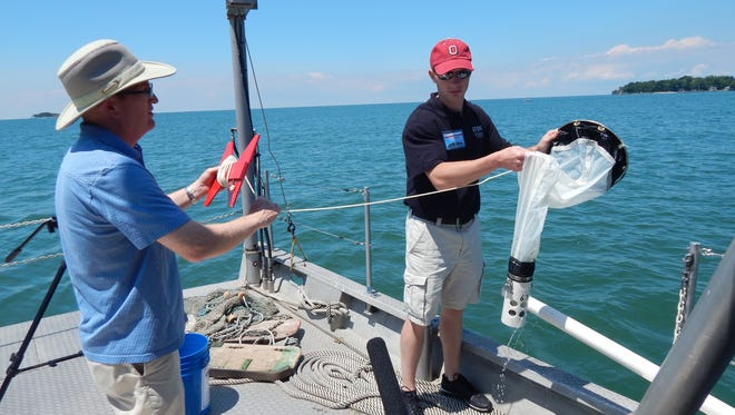 Tom Bridgeman, associate professor at the University of Toledo's Lake Erie Center, left, works with Justin Chaffin, senior researcher and research coordinator for Stone Lab and Ohio Sea Grant, to sample water near Put-in-Bay. in 2014. Ohio Sea Grant is involved in a 2017 project to have anglers scan perch from Lake Erie.