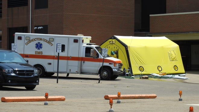 Coshocton County Emergency Medical Services ambulance and a decontamination tent were set setup outside Coshocton Regional Medical Center Tuesday. Six employees of Coshocton Municipal Court tested negative for exposure to anthrax and powder in an envelope received by the court was said to be artificial sweetener from preliminary testing.