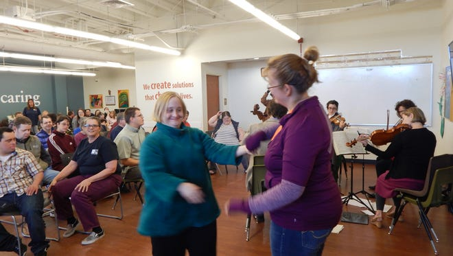 Easter Seals/Goodwill client Kristen Davies dances with  Belinda Brugman, an organization employees, during a special performance of the Great Falls Symphony.
