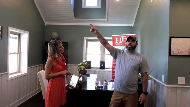 Carly Thompson looks at her husband, Jason, as he points to a window that was moved to a new spot in a cabin the couple moved from the Plainfield area. It is now the new HER Realtors office for Coshocton.