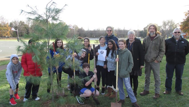 Students stand beside the newly planted space tree with (back row, from left) Readington Middle School science teacher Chip Shepherd, Principal Sharon Moffat, Dr. Jay Kelly and Dr. Neil Hendrickson.
