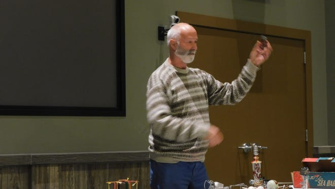 """Bob Krueger of Juneau holds up many different mystery items at the 2016 Annual """"Road Show."""""""