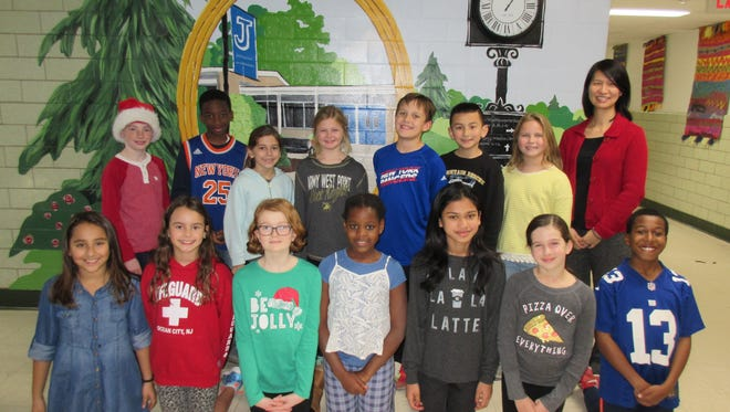 Celebrating the completion of a 160 foot mural in the Jefferson Elementary School's hallway are, standing l-r:  Westfield third graders Gavin Martin, Jayden Cummings, Sonya Seideman, Regan Stevens and Jake Florio, and fourth graders Daniel Garcia and Hannah Linsen, with Principal Dr. Susie Hung.  First row includes fourth graders Ashley Garcia and Kayla Genlot, along with fifth graders Claire Gallagher, Canya Nematadzira, Hannah Ramdath, Victoria Marmarou, and Isaiah Louison.  The group poses at the section of the mural depicting the front of the school and its clock.  A total of 290 third, fourth and fifth grade students each participated in 20-minute sessions creating scenes which represent their school and town.
