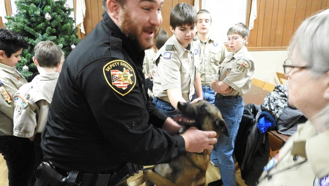 Deputy Steve Mox and K-9 officer Chili interact with members of Boy Scout Troop 403, who made a recent donation of stuff animals to the Coshocton County Sheriff's Office.