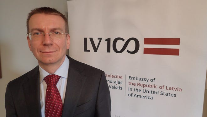 Latvian Foreign Minister Edgars Rinkēvičs poses in front of a placard celebrating 100 years of Latvian independence at his country's embassy in Washington, D.C. on March 7, 2018.