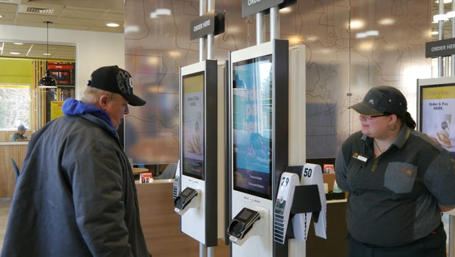 Guest Experience Lead worker Marlena Kuntz helps a customer with a self-order kiosk at the 10th Avenue McDonald's in Great Falls.