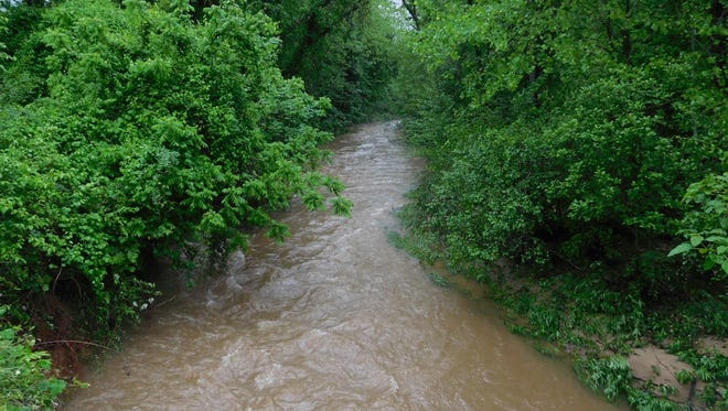 Runoff from heavy rains Thursday night and Friday morning swell Cane Creek near Miller Road in Fairview on Friday.