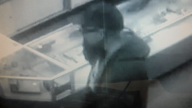 A man pretending to pawn a pair of sunglasses pulled out a gun and demanded money from a Lower Valley pawn shop is being sought by law enforcement.