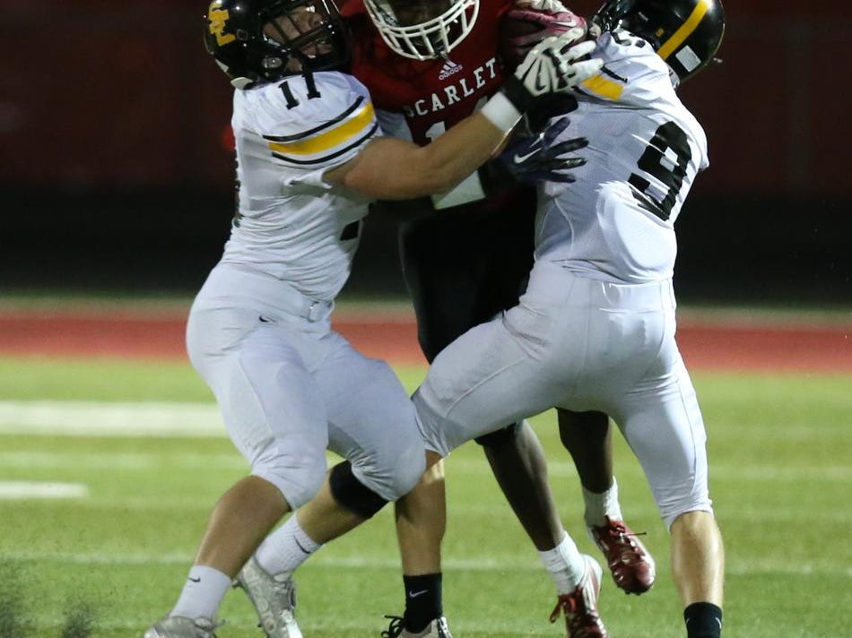 Southeast Polk's Braeden Vasey, left, and Bradley VanHeeswyk tackle Isaac Toluwalase of Des Moines East during a 56-7 win on Friday at Williams Stadium.