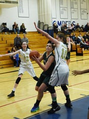 Spackenkill's Bailey Riley, center, goes for a layup while FDR's Kamryn Hammond, left, and Sara Miller, right, defend during a Holiday Classic game held in Pine Plains.