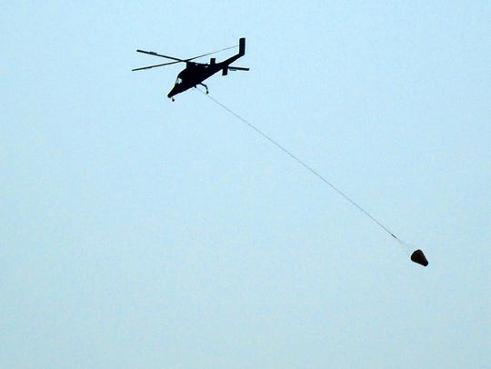 A K-Max Heavy lifting helicopter flies back to the