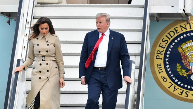 President Donald Trump and First Lady Melania Trump walk down the stairway of Air Force One as they arrive at Melsbroek Military airport in Melsbroek, Belgium, TuesdayTrump is in Brussels to attend a two-day NATO summit.