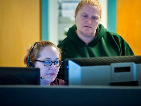 Lindsay Cronin (left) and Chrystal Yantz work on a call at the 911 call and dispatch center at the Vermont State Police barracks in Williston in December 2014.