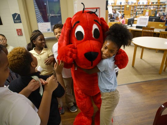 Ten-year-old Quiajha Whalen, a fourth-grader at Harlan Elementary School, got a hug from Clifford the dog after visiting a portable library where she and fellow classmates got to pick out free books to take home.