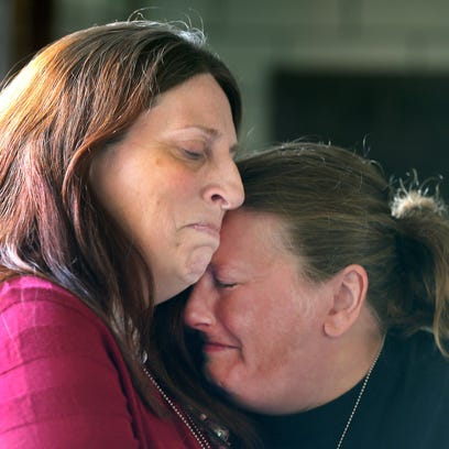 Laura Meehan, right, is comforted by her sister Wendy