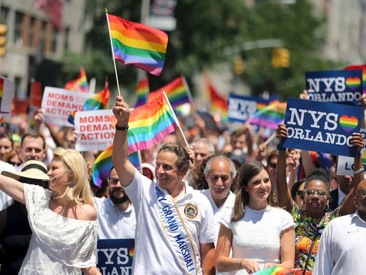 FILE - In this June 26, 2016, file photo, New York Gov. Andrew M. Cuomo, center, waves a flag as he walks in the New York City Pride Parade in New York. Duke has an opening on its men's basketball schedule because of the state law that impacts LGBT people. The Blue Devils were supposed to play Albany on Nov. 12 as part of the Hall of Fame Tipoff tournament but there's no opponent listed on that day in Duke's schedule that was released Wednesday, July 13. Holly Liapis, spokeswoman for the State University of New York system that includes Albany, says that game won't be played because of Cuomo's executive order banning publicly funded, non-essential travel to North Carolina. Cuomo's order is in response to a North Carolina law that opponents say can allow discrimination against LGBT people. (AP Photo/Mel Evans, File)