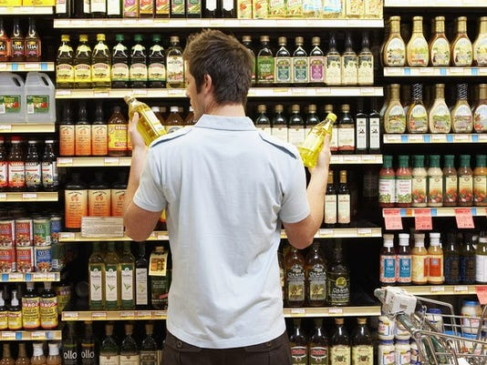 young-man-comparing-bottles-grocery-shopping-crop_large.jpg