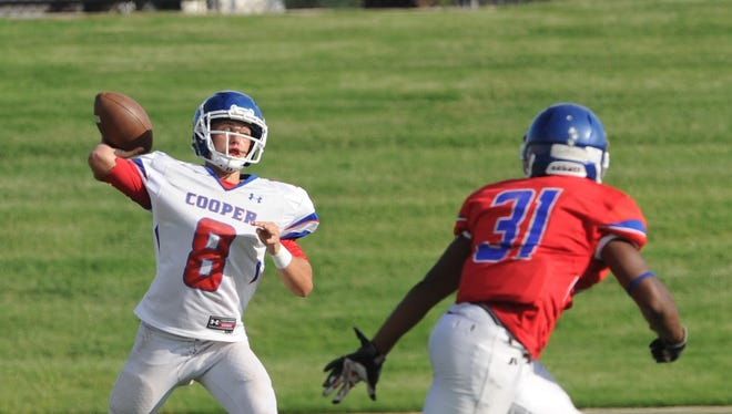 Cooper quarterback Henry Ferrel (8) gets ready to throw a pass as James Griffin (31) defends during the Cougars' annual Red & Blue spring football game on May 24 at Shotwell Stadium.