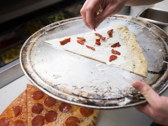 A slice of pizza is prepared in the kitchen at Pizza
