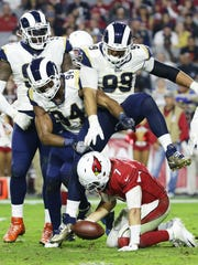 Rams defenders celebrate after Cardinals quarterback Blaine Gabbert tripped and fell in the fourth quarter on Sunday.