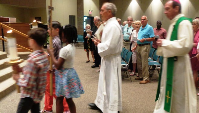School children lead Archbishop Dennis M. Schnurr in the entrance procession for the Laudato Si' recognition prayer service held at Community of the Good Shepherd Church, June 18.