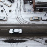 Tire tracks in snow mark where cars have driven along Jefferson Avenue on Wednesday, March 4, 2015. Winter weather hit the Ozarks in the early morning bringing with it sleet, snow, and freezing temperatures.