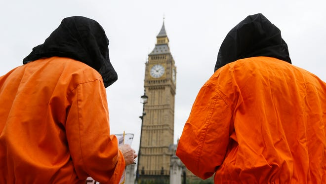 In this file photo dated Oct. 15, 2014, protesters wearing suits and masks protest against the Guantanamo Bay detention camp, in Parliament Square in London, with Big Ben's clock tower in background.