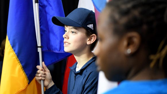 Ball kid Andrew Tashie holds a flag as he prepares