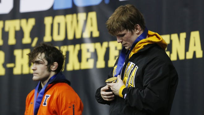 Iowa's Cory Clark looks over his medal after defeating Illinois' Zane Richards Sunday.