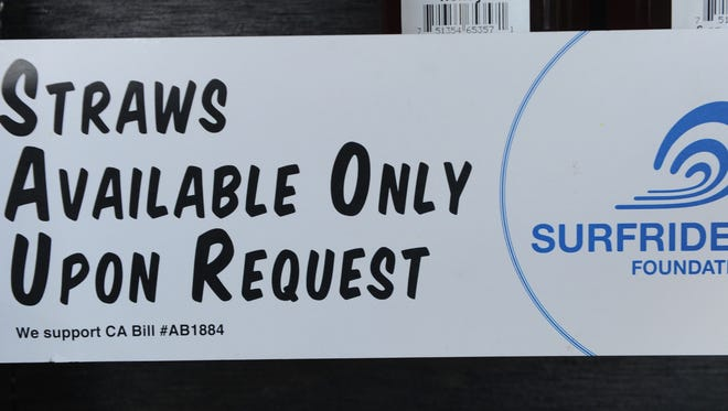 """A posted sign alerts customers to the straw policy at the Harvest Café in Ventura, California. Surfrider Foundation has recognized the restaurant as """"Ocean Friendly,"""" in part because it doesn't use plastic straws and provides straw only upon request."""