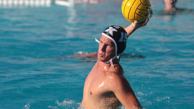 Xavier College Prep's Gus Kelly shoots and scores against  Palm Spings on Thursday, October 16, 2014 at the Palm Desert Aquatic Center.