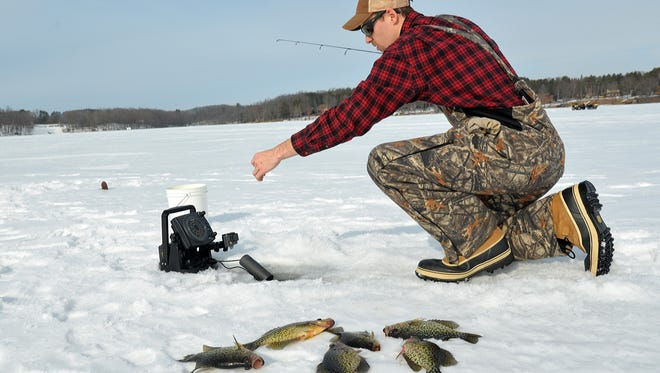 Cody Larsen tries to add to his catch while jigging for crappies on Turtle Lake.