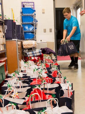 Nikolas Potter, a Locust Grove Elementary School student, moves care packages put together for A Christmas Smile into a storage room in this December 2012 file photo. Organizers are seeking donations for this year's event, which is in its 13th year.