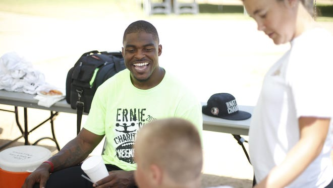 Ernie Sims laughs with a camper at his BIG H.I.T.S. Foundation Football and Cheer Camp at Tom Brown Park on Friday.