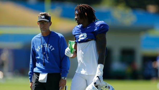 UK offensive coordinator Eddie Gran talks with wide receiver Dorian Baker talk during UK Football Fan Day open practice at Joe Craft Football Training Facility in Lexington, Ky., on Saturday, August 5, 2017.