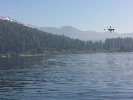 A firefighting helicopter gathers water from Lake Siskiyou