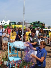 Renee Ebert assists with releasing a batch of butterflies in honor of her late daughter, Britney following opening ceremonies of Farm Technology Days, July 11, 2017.