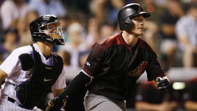 Diamondbacks hitter Chris Herrmann (right) watches his RBI single in front of Rockies catcher Nick Hundley during the seventh inning at Coors Field in Denver on June 24, 2016.
