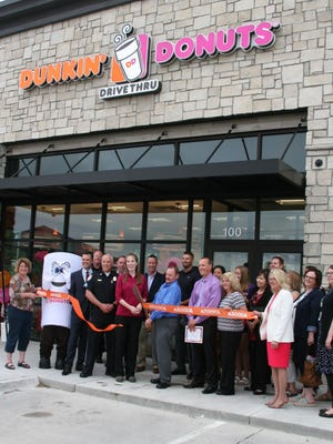 Altoona Chamber of Commerce members smile for a photo as Dunkin' Donuts owner Chris Benge cuts the ribbon at his newest franchise in Altoona.