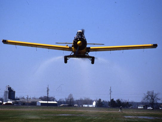 A crop duster at work over a Sussex County field.