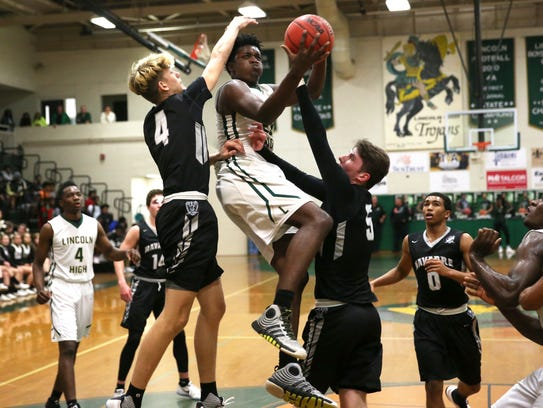Lincoln's Darrion Fluker tries to lay the ball up past