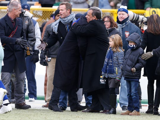 New Jersey Gov. Chris Christie, center right, embraces a person on the sidelines before an NFL divisional playoff football game between the Green Bay Packers and Dallas Cowboys Sunday, Jan. 11, 2015, in Green Bay, Wis. (AP Photo/Mike Roemer)