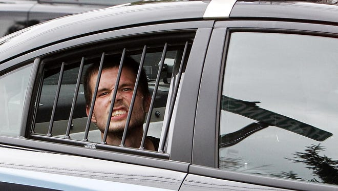Zachary Johnson, the second burglary suspect, snarls as he sits in a police car after being caught at Ninth Street and Harrington Drive.