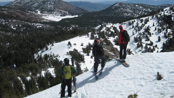 Three backcountry skiers contemplate their lines on public land overlooking Lake Tahoe in Nevada.